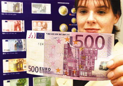 ¼Úù¶r²¼¡B²{¶rAline Heurley from Flensburg checks a 500-Euro bank note in front of a poster showing the new Euro currency during a public presentation of the new Euro at the branch office of the German Federal Bank in Flensburg, northern Germany, on Saturday, Sept.1, 2001. The new currency will be introduced on Jan.1, 2002, in twelve European countries. EDS note: Bank note is perforated 'invalid' because of security reason during public presentation. (AP Photo/Heribert Proepper)
